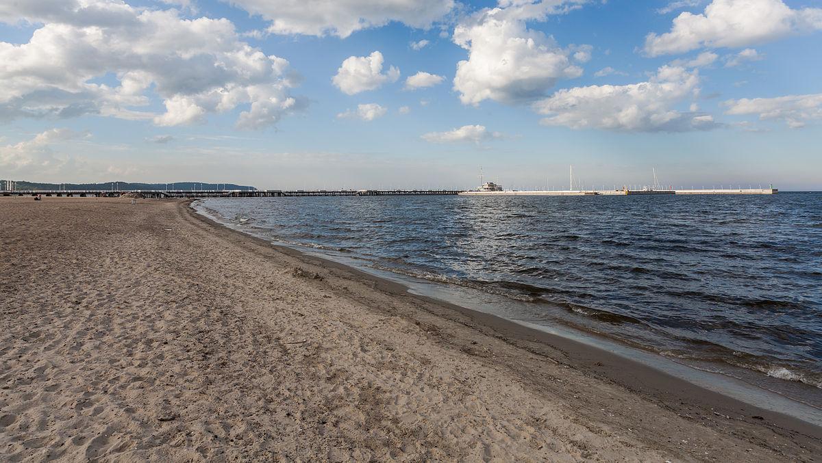 Písečné pláže, čisté moře a v pozadí molo, Diego Delso
